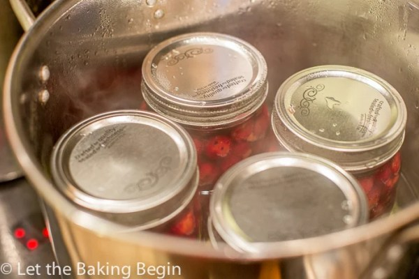 Closed mason jars in a pot in boiling water.