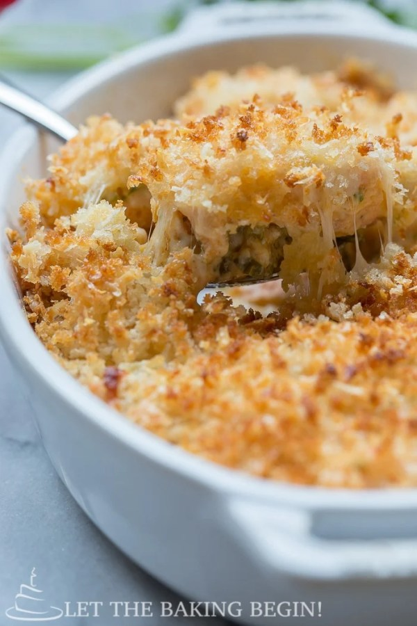 Cheesy Parmesan Crusted Salmon Bake in a casserole dish with a spoon.