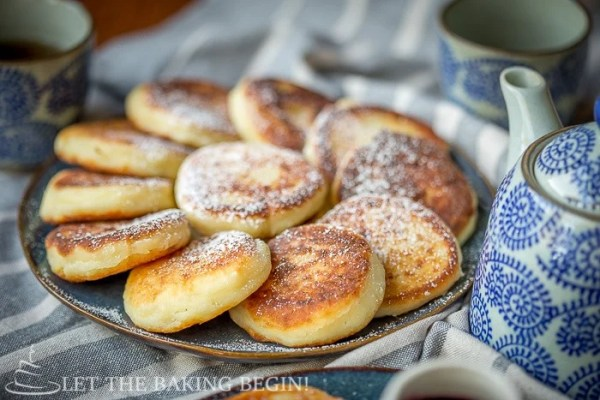Ricotta Pancakes on a plate topped with powdered sugar.