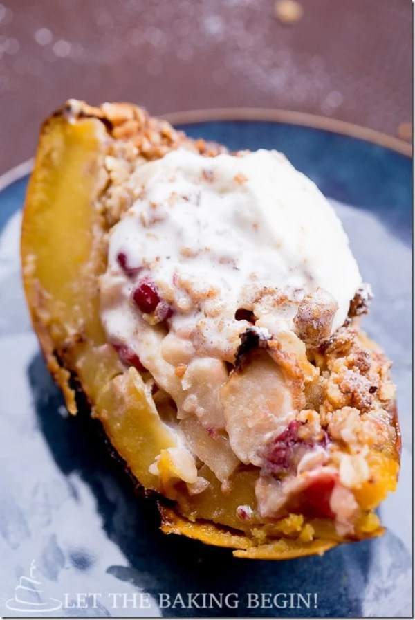 A slice of acorn squash with an apple and cranberry filled topped with whipped cream.
