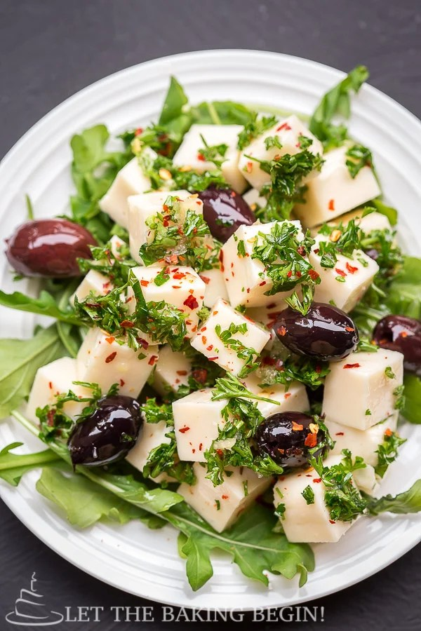 Marinated cheese appetizer on a plate with olives and topped with fresh chopped greens.
