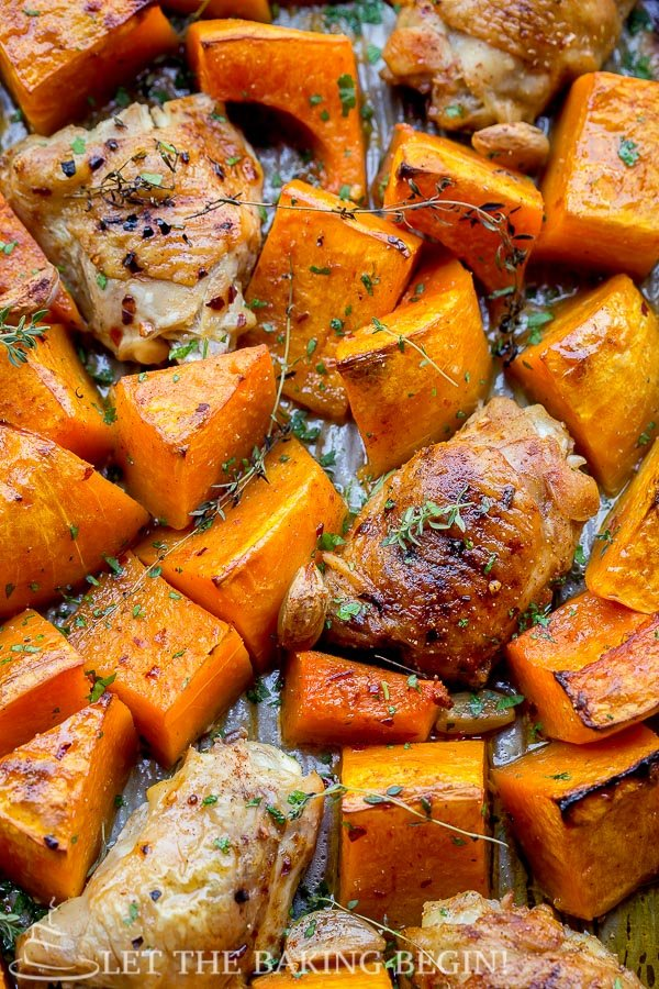 Roasted chicken thighs and butternut squash in a baking sheet topped with rosemary.