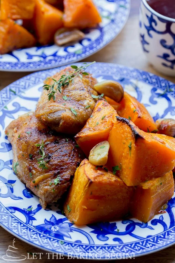 Baked chicken thighs and roasted butternut squash on a blue plate topped with fresh rosemary.