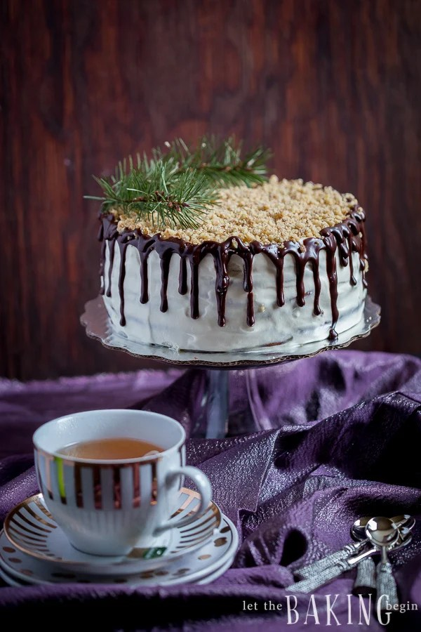 Chocolate cake with plums, walnuts and sour cream on a cake stand next to a cup of tea.