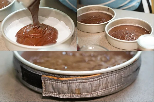Chocolate batter is divided into two cake forms lined with parchment. Cake strip is placed around the form.