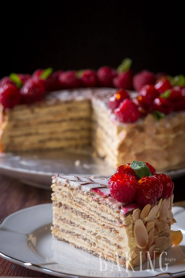 A slice of Esterhazy cake topped with fresh raspberries in a plate.