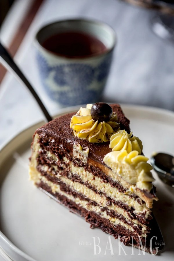 A slice of chocolate cake with layers of custard buttercream on a plate.