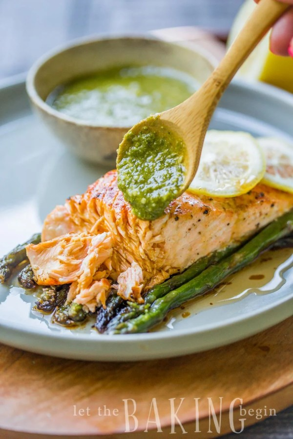 Baked salmon and asparagus on a plate with chimichurri sauce.