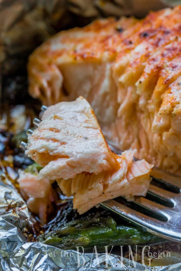 Salmon fillet in foil with asparagus and a fork of salmon.