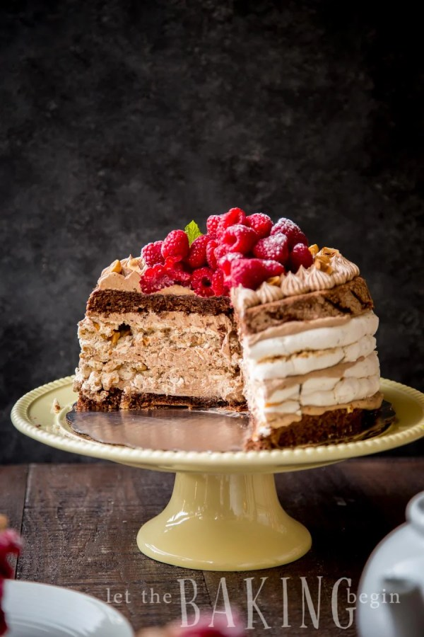 Hazelnut Meringue cake on a cake platter with a slice missing.