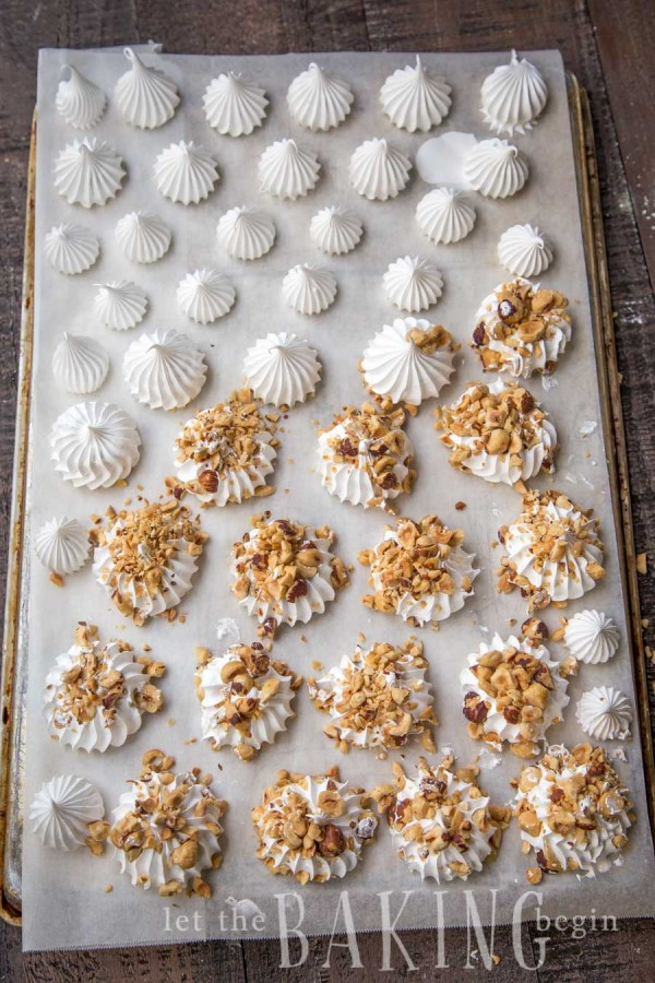 Half meringues on a parchment-lined a baking sheet with half of the half meringues topped with hazelnuts.