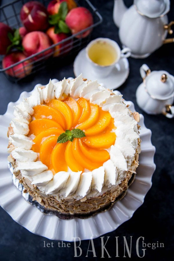 Peaches and cream cake on a cake platter next to a tea set.