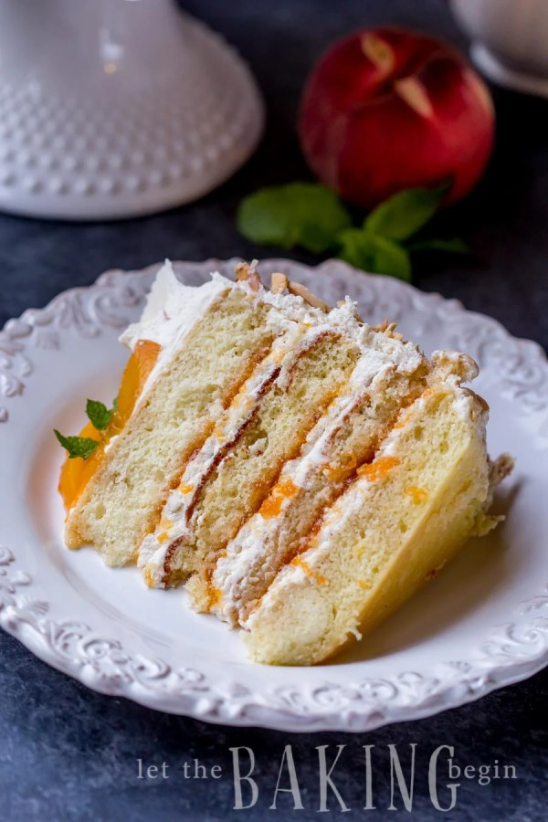 A slice of peaches and cream cake on a plate with peach jam and Chantilly cream.