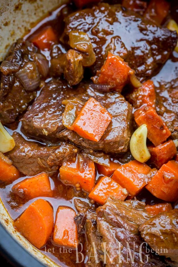 Close up picture of braised short ribs, carrots, onions, and garlic in stock in a dutch oven.