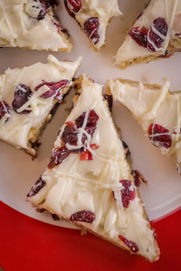 Cranberry Bliss Bars on a plate topped with cranberries and white chocolate drizzle.