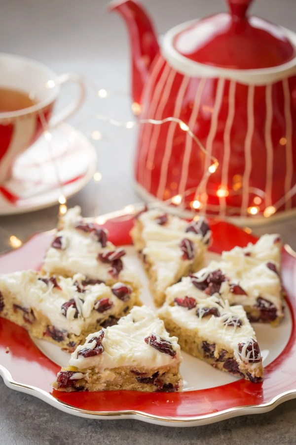 Cranberry Bliss Bar - Blondie base layer, which is generously speckled with white chocolate chunks and dried cranberries, then topped with orange flavored cream cheese frosting, sprinkled with more cranberries white chocolate drizzle.