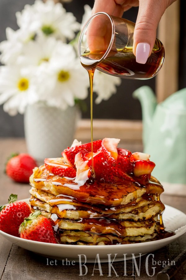 Maple syrup being poured onto a plate of cottage cheese pancakes topped with fresh strawberries.