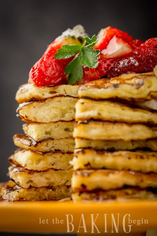 Sliceless stacked pancakes topped with fresh strawberries on a yellow platter.