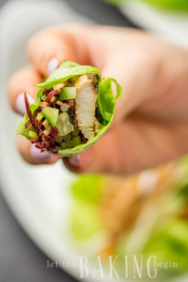 A bitten into lettuce wrap with cucumbers and Thai chicken.