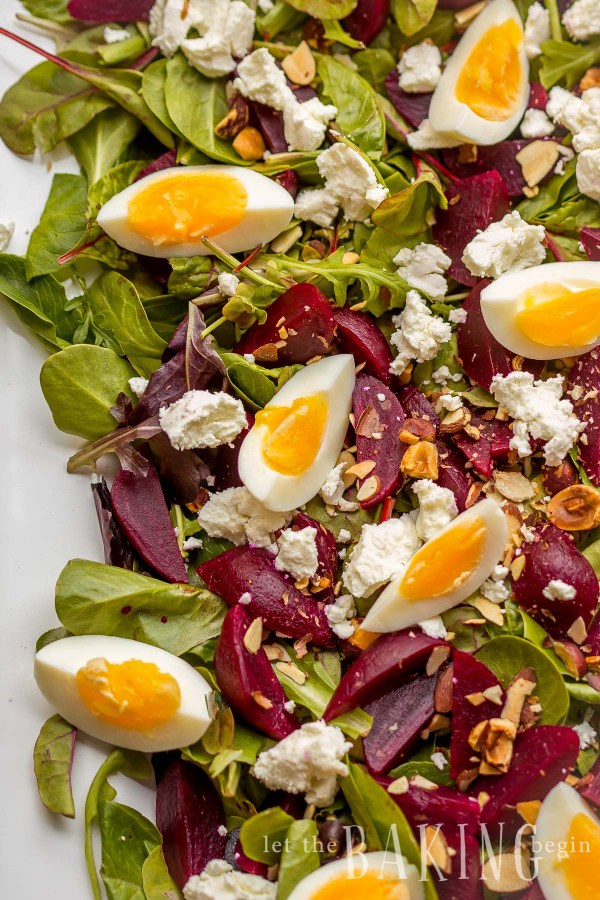 Beet and Goat Cheese Salad with Egg is served on a bed of Spring Mix Salad, then sprinkled with Goat Cheese, Hazelnuts and Egg on a platter.