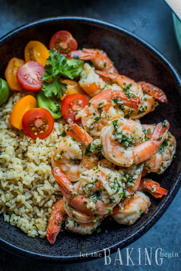 Shrimp with cooked rice and tomatoes with fresh greens in a white bowl.