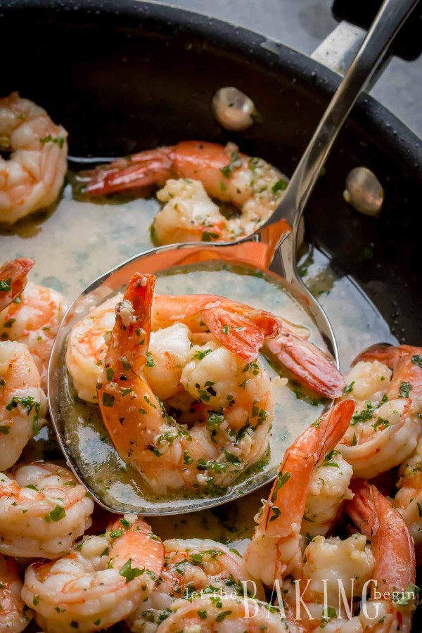 Shrimp scampi in a skillet with butter sauce and fresh parsley.