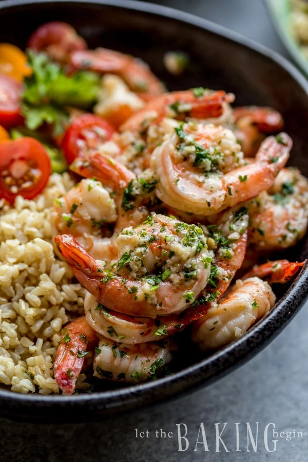 Close up picture of shrimp with fresh greens in a bowl with rice and tomatoes.