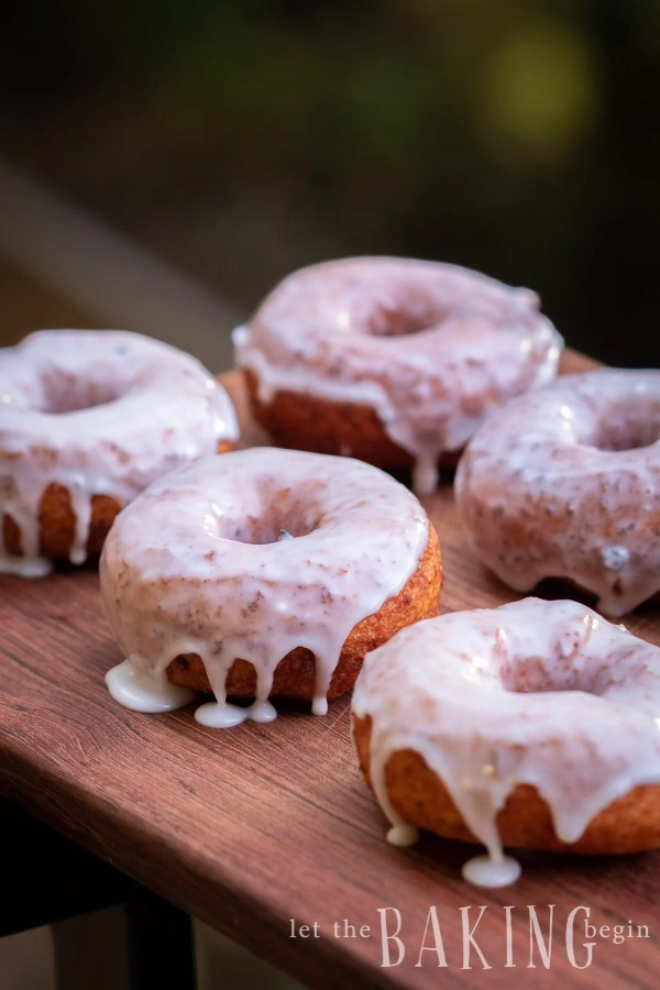 Fried Donuts filled with lots of protein, covered with sugar glaze, placed on a board.