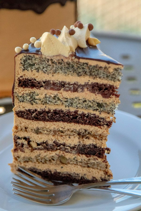 Russian Cake (Korolevskiy Cake)- Layers of walnut, poppyseed, cherry and chocolate cakes frosted with Dulce De Leche Buttercream and drizzled with chocolate.