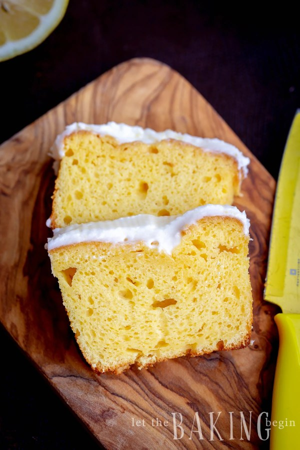Sliced lemon loaf cake on a cutting board with a yellow knife.