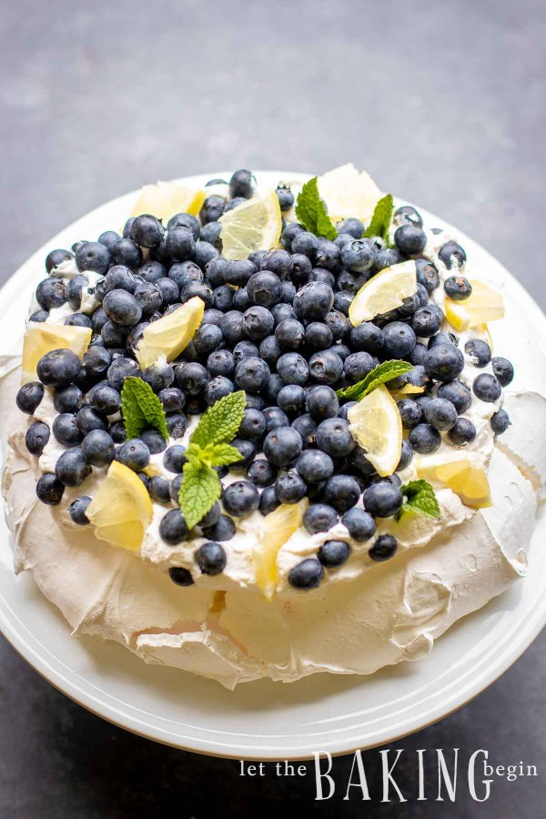 Pavlova cake topped with fresh cream, lemon wedges, blueberries and mint.