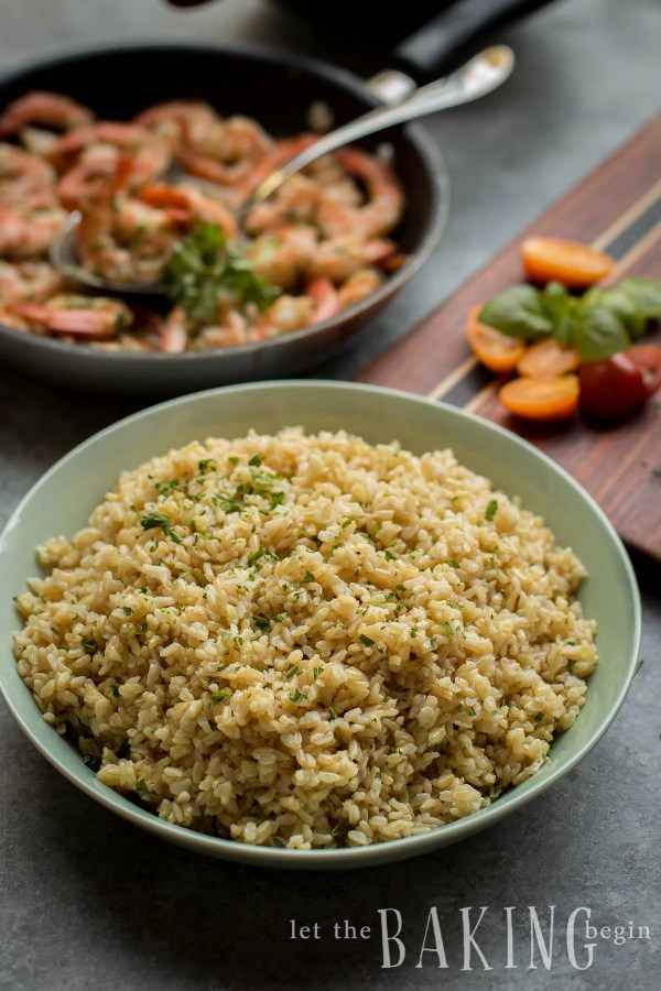 Instant Pot brown rice in a bowl sprinkled with fresh herbs.
