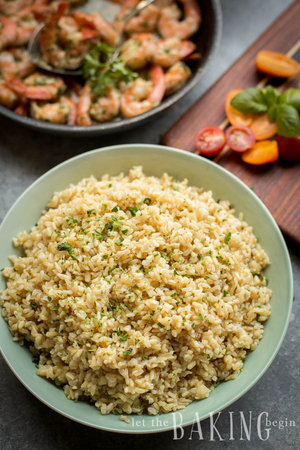 Pressure cooker brown rice in a bowl with a skillet of shrimp in the background.
