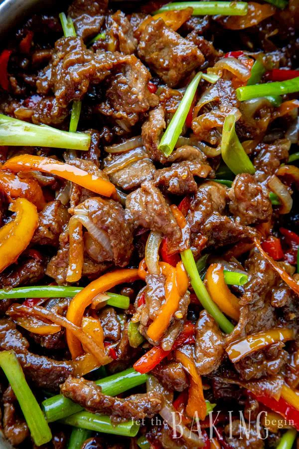 Close up image of Mongolian beef with meat, peppers and onions in sauce.