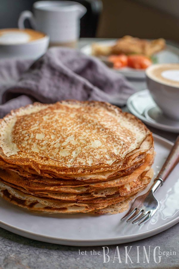 Stack of blinis on a plate with a fork.