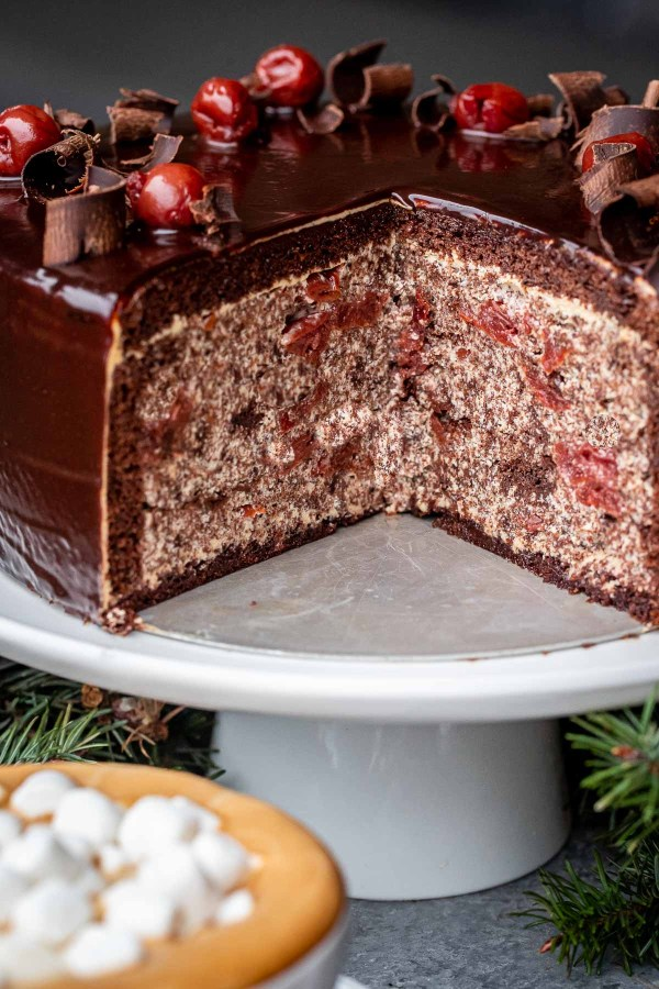 The Chocolate Cherry cake on a cake stand with a piece removed, showing off the inside of the cake.