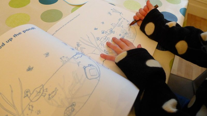 child working on Okido colour me activity book from thamed and hudson