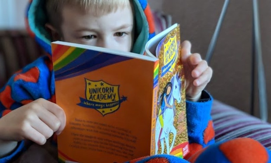 child reading unicorn academy book