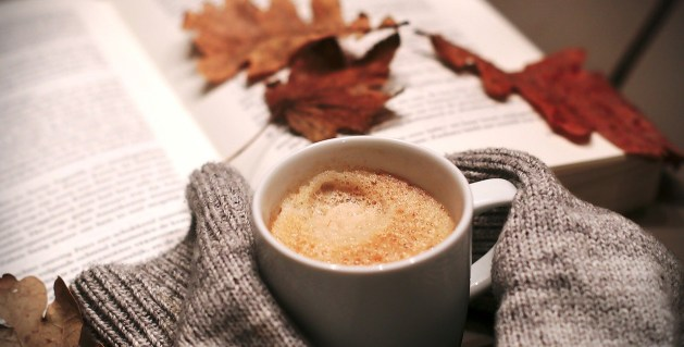 Pensieri sparsi: scrivere, contrarsi, fluire   Tazza di caffè tra le mani coperte da un maglione davanti a un  libro con delle foglie rosse sopra