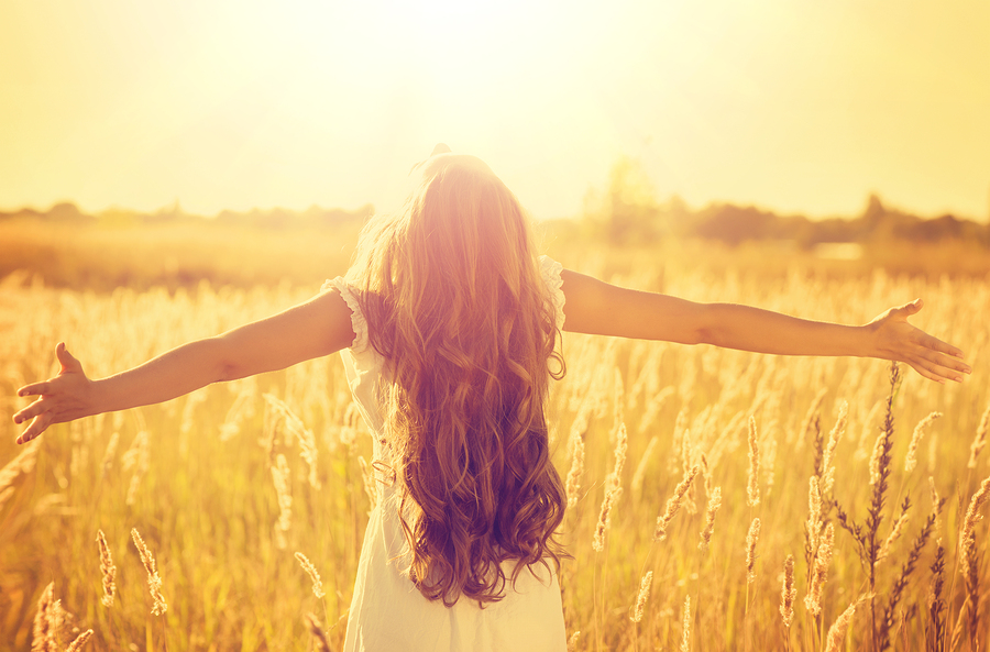 Girl with arms outstretched in nature   embracing life's challenges