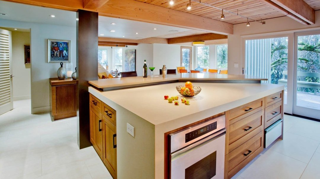 A modern kitchen remodeling project in Portland, OR featuring wooden ceilings, stone countertops, and sleek lighting.