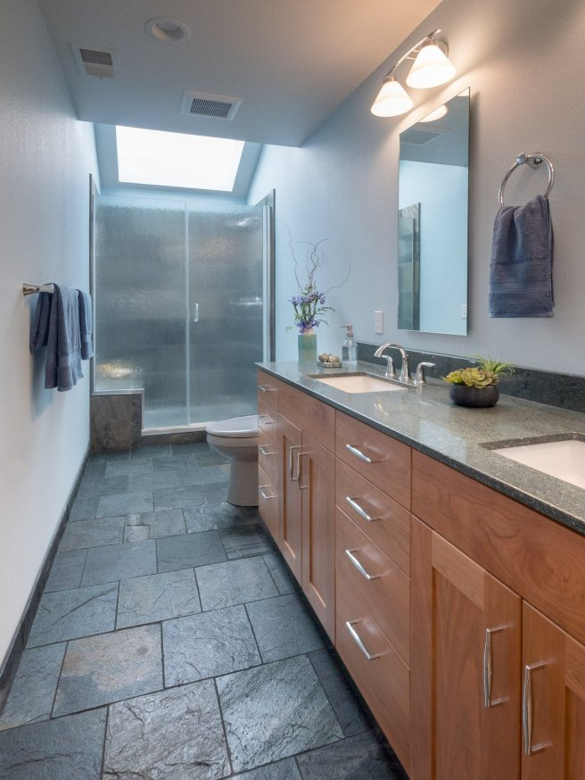 Transitional style bathroom with wood cabinets and stone floors
