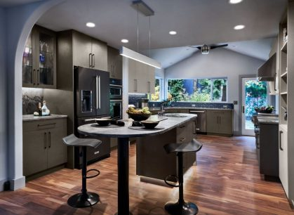a kitchen island with decorative bowls on the counter and a black fridge in the background with a view of a glass door leading into a yard