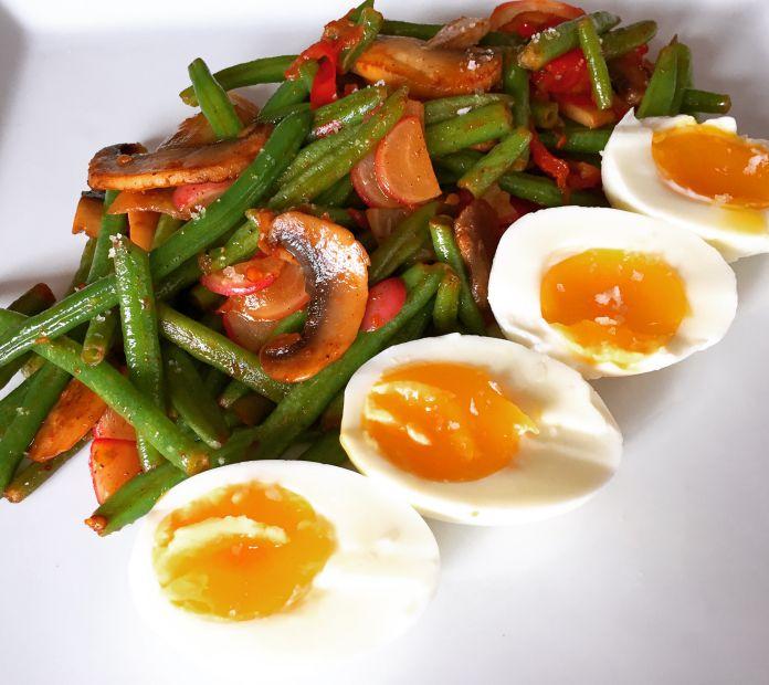 Smør-sauteret grønt med smilende æg