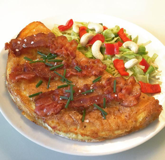 Stor grøntsagsomelet med sprød bacon, frisk purløg og blandet salat