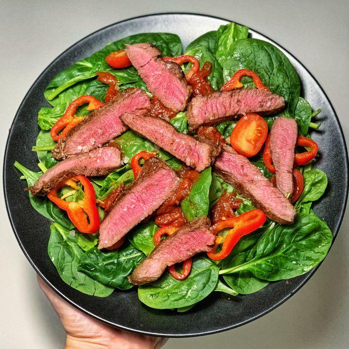 Spicy oksesteak-spinatsalat med peberfrugt, tomat og tacosovs