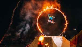 man jumping on snowboard through fire circle at night
