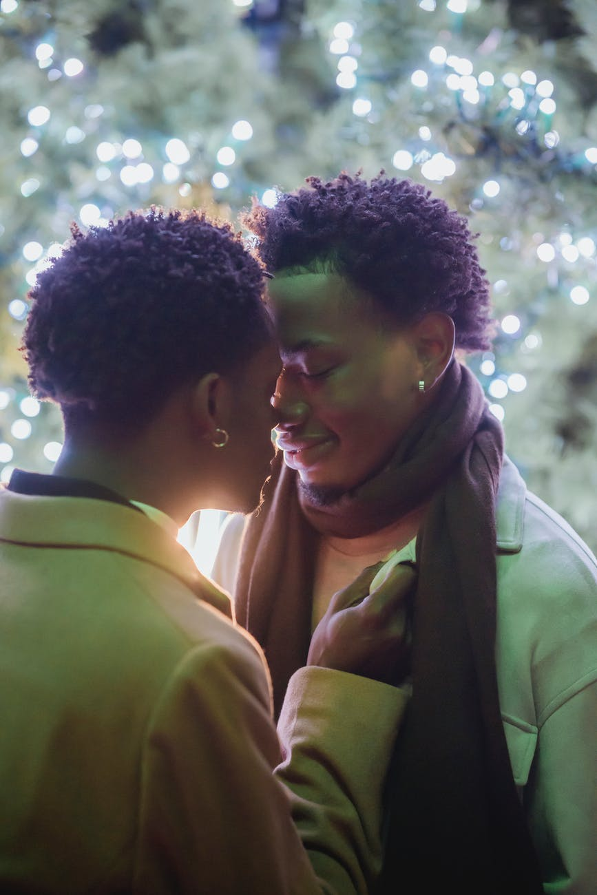 happy young black gay couple hugging with closed eyes on street at night