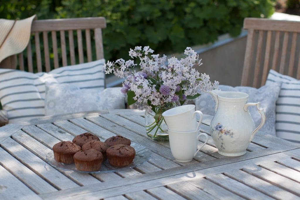 Fikapaus med chokladmuffins och lila syrener i vas.