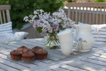 Vackert trädgårdsbord i teak med lila blomsterbukett.